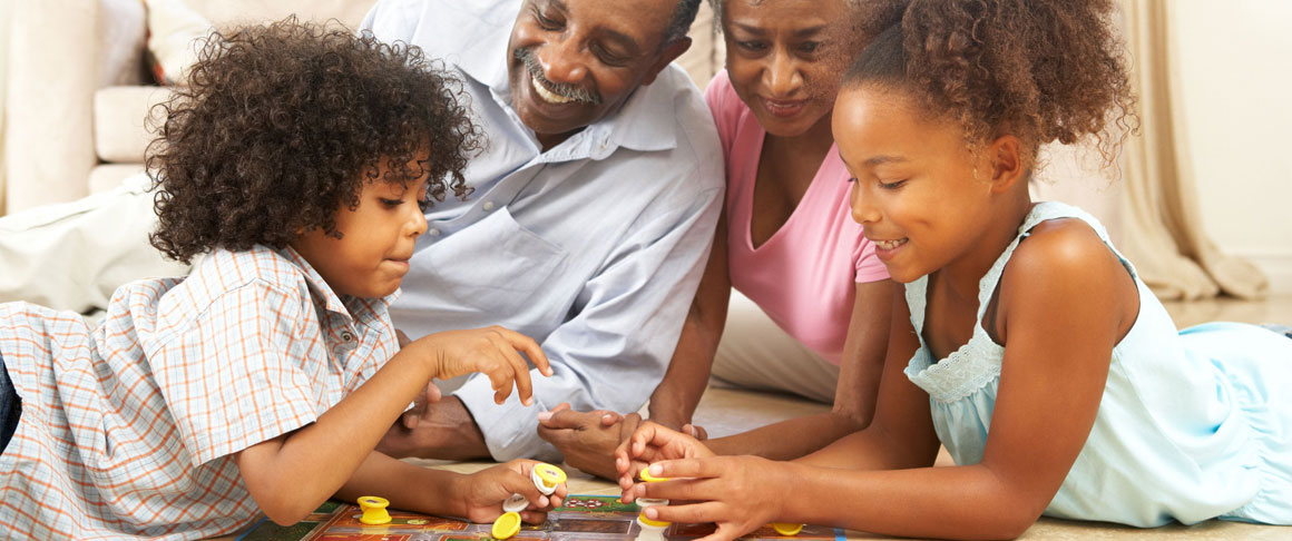 Black-American children playing a board game with grandparents