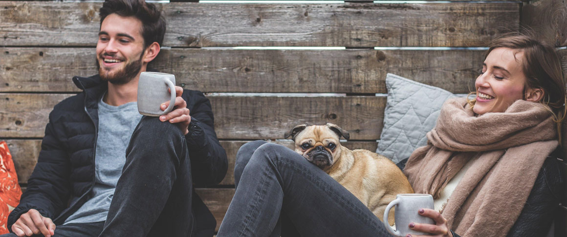A young couple drinking coffee with a dog